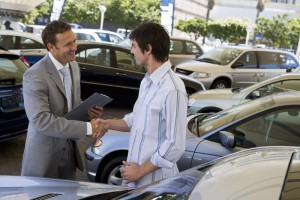 Salesman zeigt Mann, der ein Auto
